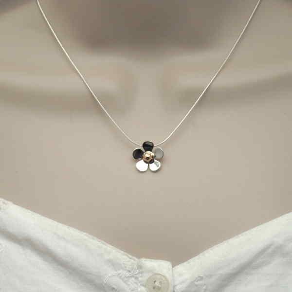 small daisy pendant on neck