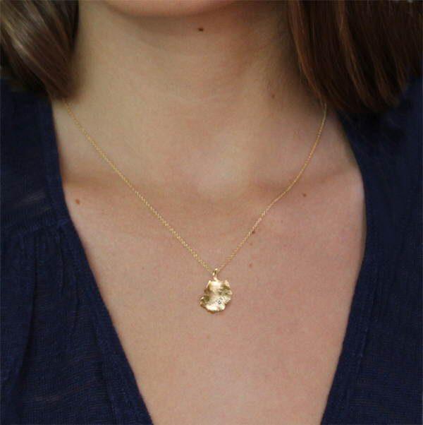 18ct gold and diamond leaf pendant on neck
