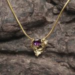 18ct gold and amethyst necklace on wood background